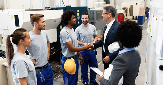 Executive shakes hands with workers on factory floor