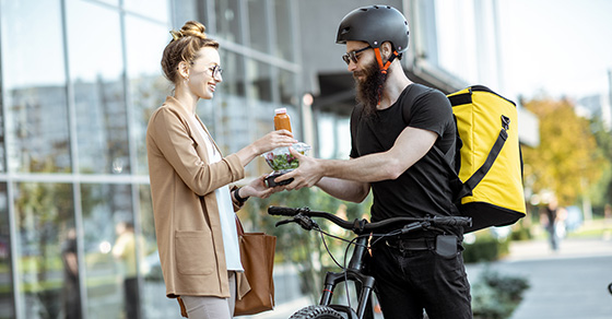 Bike messenger delivers a salad and beverage to a woman outside a building.